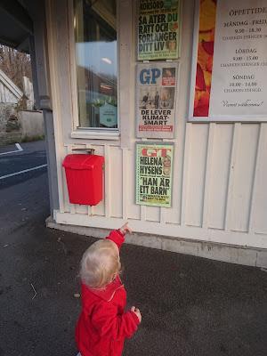 Lilla Eila ser en löpsedel där hennes mamma Maja är med