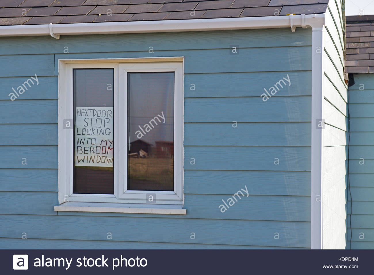 sign-on-window-of-wooden-chalet-warning-neighbour-not-to-look-into-KDPD4M.jpg