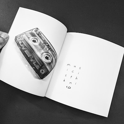 "An open page of the ""music maze,"" typography art and photo of a classic cassette tape."