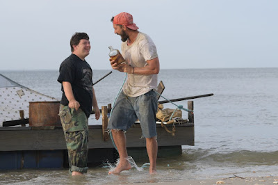 "Shia LaBeouf and Zack Gottsagen step off of their makeshift raft onto a beach and have a drink in a movie still for the feel-good comedy drama film ""The Peanut Butter Falcon"""