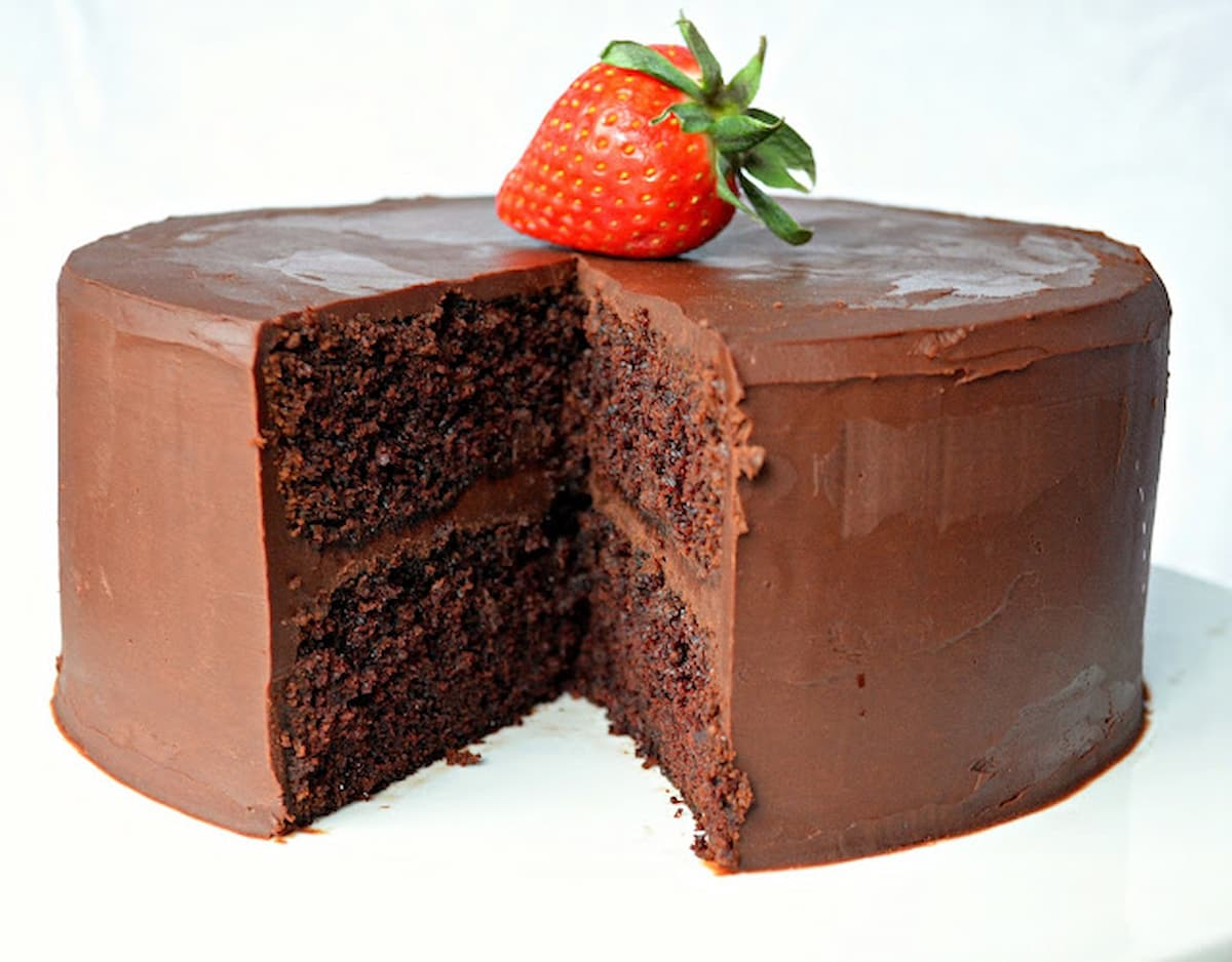 Moist Chocolate Cake with Ganache Frosting with a slice missing on a white cake platter with a strawberry on top.