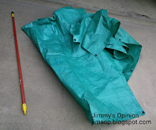 Red broom handle and green tarp lying on a concrete driveway