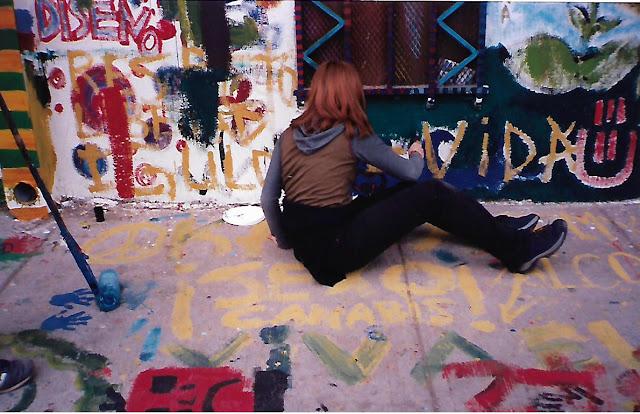 """Adolecente pintando un mural callejero en la fiesta cultural """"Santiago amable"""". La consigna sobre la que está sentada dice """"sexo y cannabis""""."""