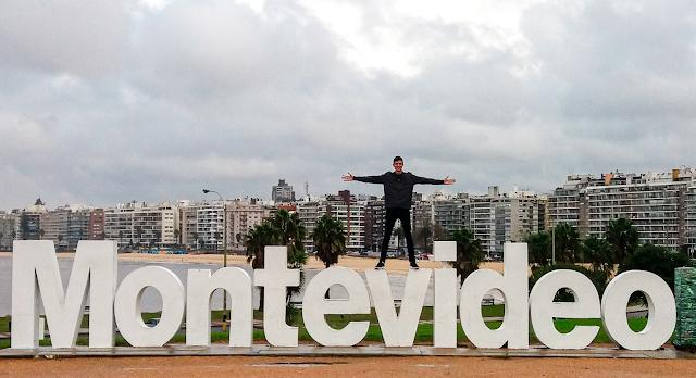 Menina em cima do letreiro escrito Montevideo, com a cidade atrás