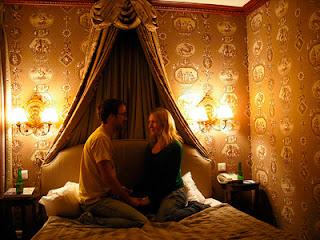 Imagen de un hombre y una mujer sentados en una cama