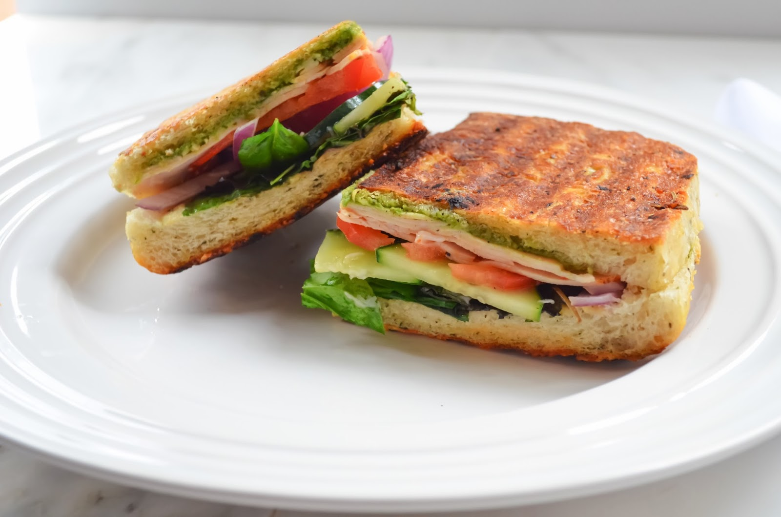 Turkey Pesto Paninis filled with Turkey, Tomato, Onion, and Spinach on Focaccia Bread.