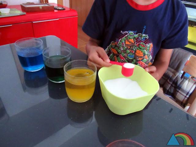 Añadiendo azúcar a agua de colores para aumentar su densidad