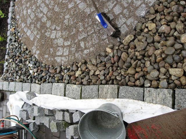 En sirkel av brostein blir til i Furulunden, elvestein lempes på plass på utsiden av sirkelen