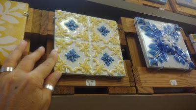uma mão tocando num azulejo numa prateleira