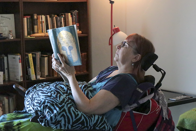 Reclining in her chair, Jennifer reads in her living room