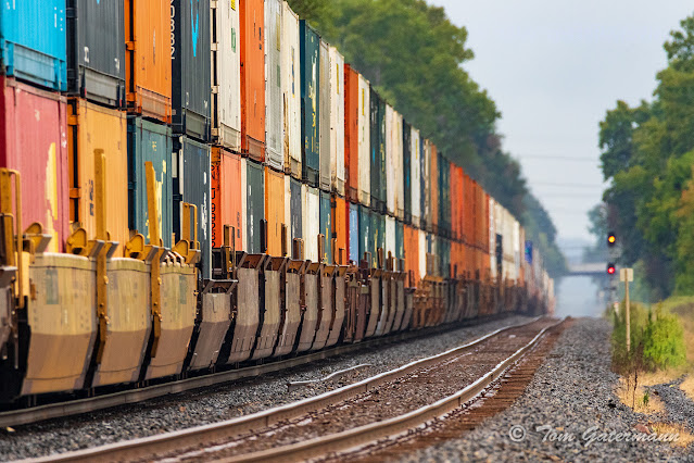 Colorful containers sit in well cars on CSX train Q004-14