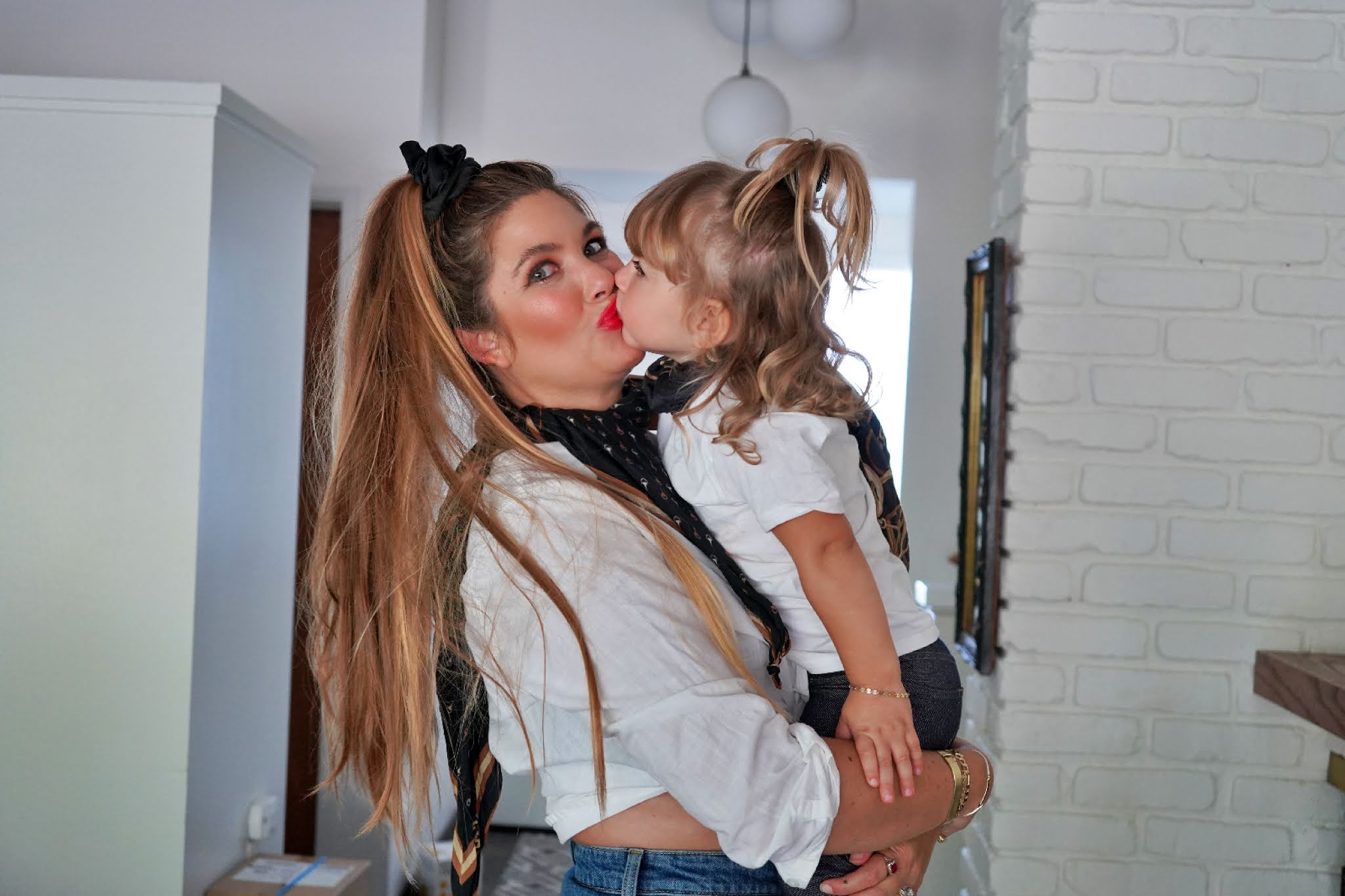 kid kissing her mom on the lips