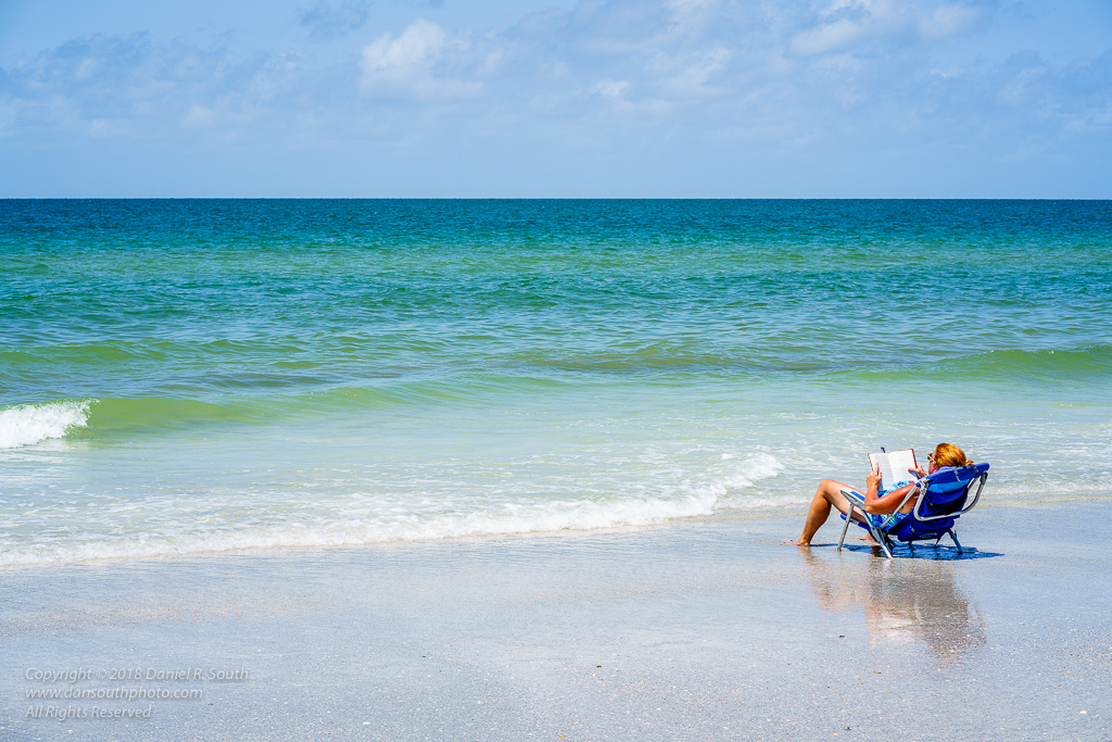 a photo of a woman reading a book on a florida beach