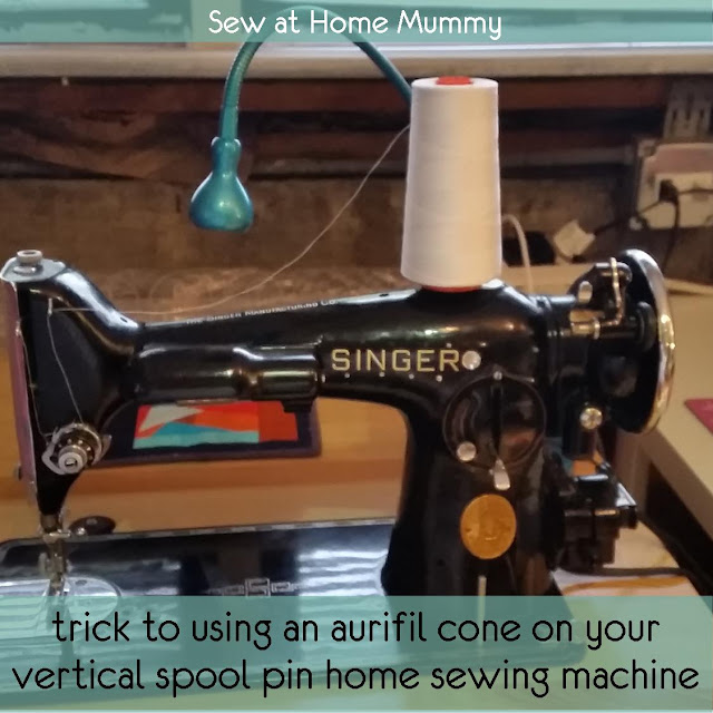 Sew at Home Mummy  |  place a narrow spool of thread on your vertical spool pin, then, slide your cone over top.The narrower spool should extend the purpose of the pin enough to hold your cone in place!  * you may need to play a bit with the size and type of smaller spool which will fit under the cone with out obstructing it's spinning motion while sewing.