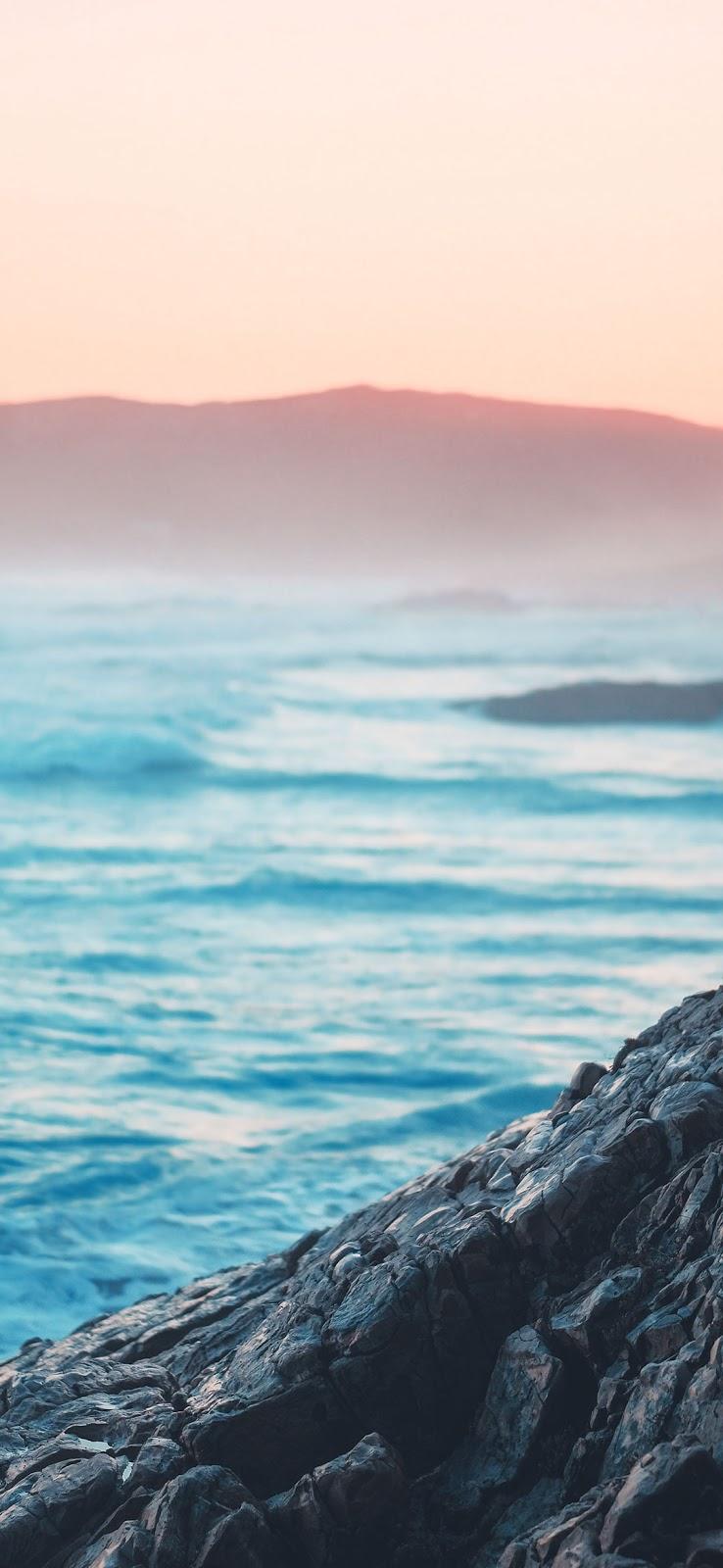 خلفية التقاء مياه البحر الزرقاء بشاطئ الصخور البركانية