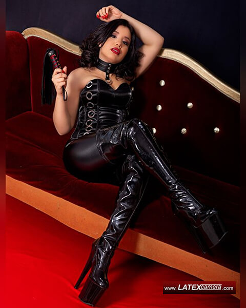 Brunette Dominatrix SkarlethSarai on latexcamera in black PVC overknee boots hoding black flogger