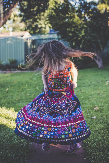 little girl twirling in colourful skirt