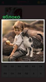 на бревне сидит мальчик с яблоком и рядом ходит кошка