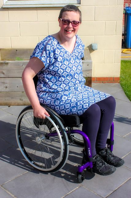 I'm sitting in my new Kuschall wheelchair. It has a purple frame which is all new and shiny. The wheels are a just standard wheels.