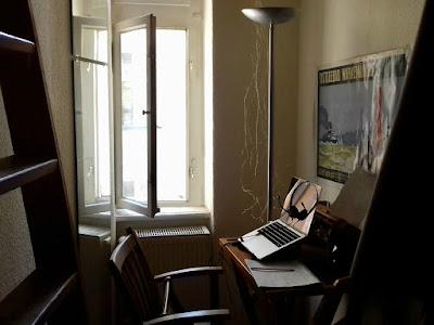 Fenster, Leiter zum Hochbett, Spiegel, schmales Fenster, Tisch und Stuhl, Computer mit Kopfhörer, rechts angeschnitten der Ärmel einer Anzugjacke