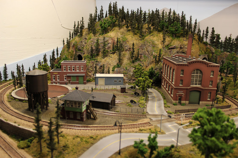 Completed industrial scene including rail yard, water tower, turn table, signal tower and various model building kits