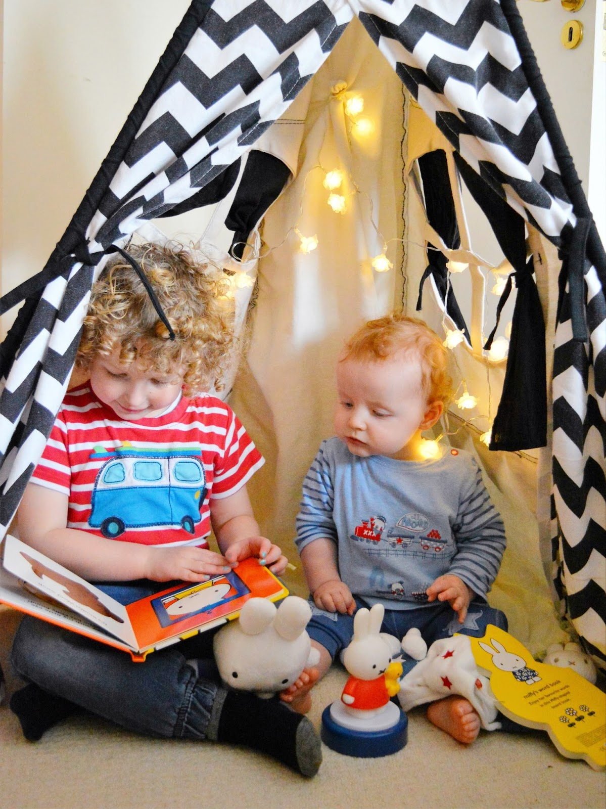 Children in a teepee reading