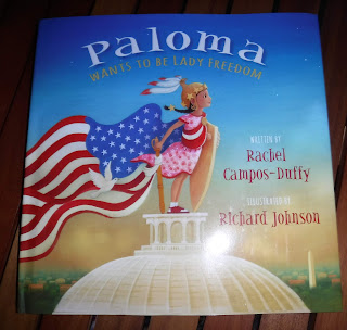 front cover of picture book Paloma Wants to Be Lady Freedom by Rachel Campos-Duffy, featuring an illustration of a hispanic girl dressed as lady freedom and standing on top of the US Capitol Dome