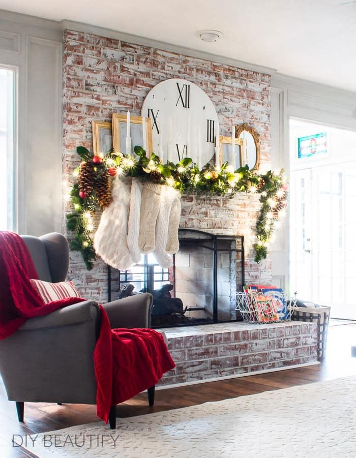 Christmas fireplace with full garland, candles and mirrors
