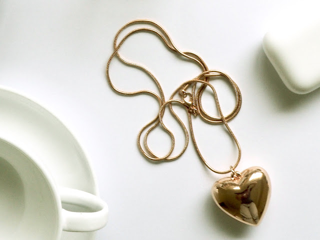 Gold necklace with a heart pendant display on top of a white table