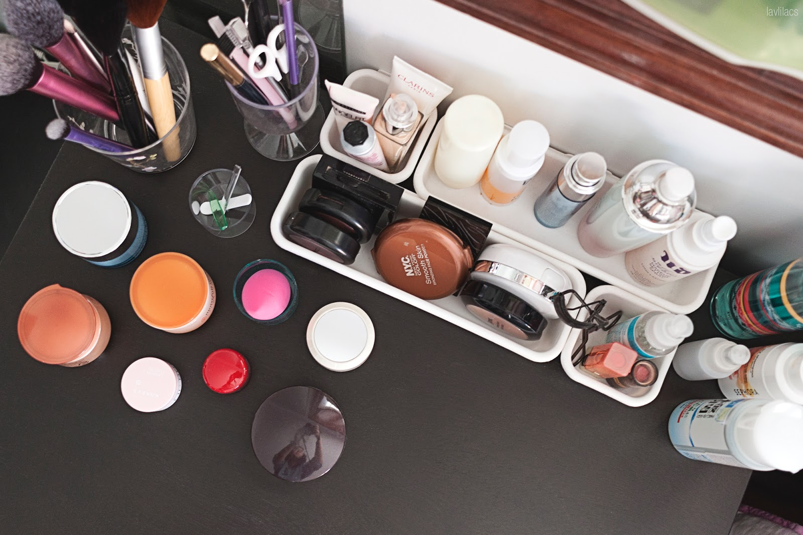 Daily makeup skincare products on top of bedside table aerial view
