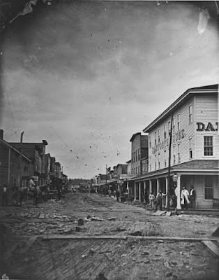 Black and white photo of street scene around 1865 with dirt street and two story buildings lining either side. People are standing in front of building to the right and a man sits on a horse on the left side of the street
