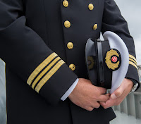 PIc of torso of ship's captain in uniform holding hat under arm, shiny buttons and braid around sleeves