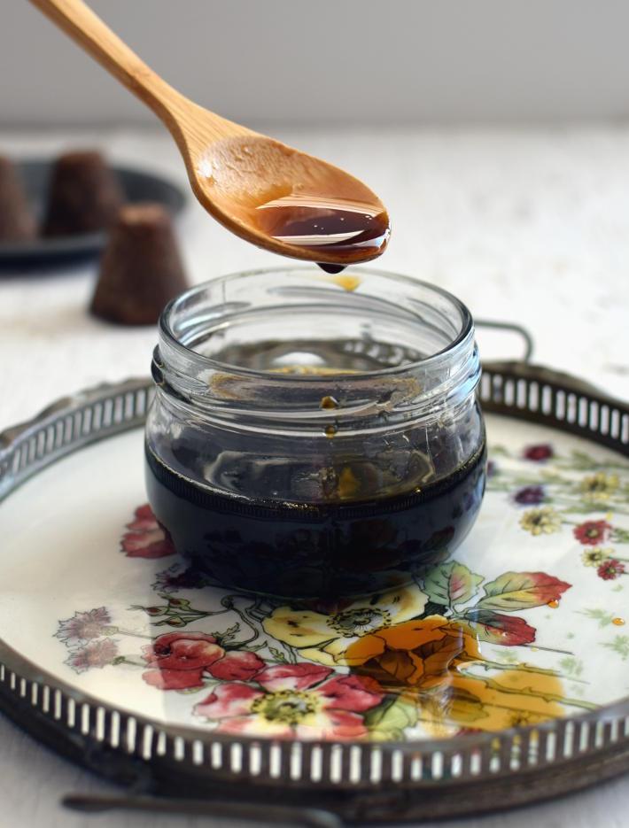 Miel de panela en una envase de vidrio con una cuchara de madera