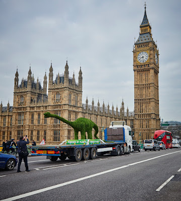 Florasaurus passing big ben and the houses of parliament in London