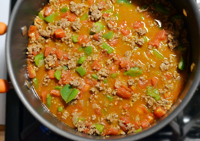 Once the peppers have softened add the crushed tomatoes and stir to ...