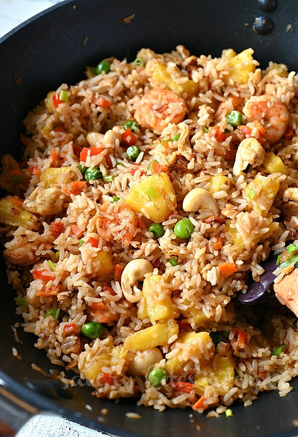 another look of a black wok with homemade authentic thai pineapple fried rice with lots of cashews