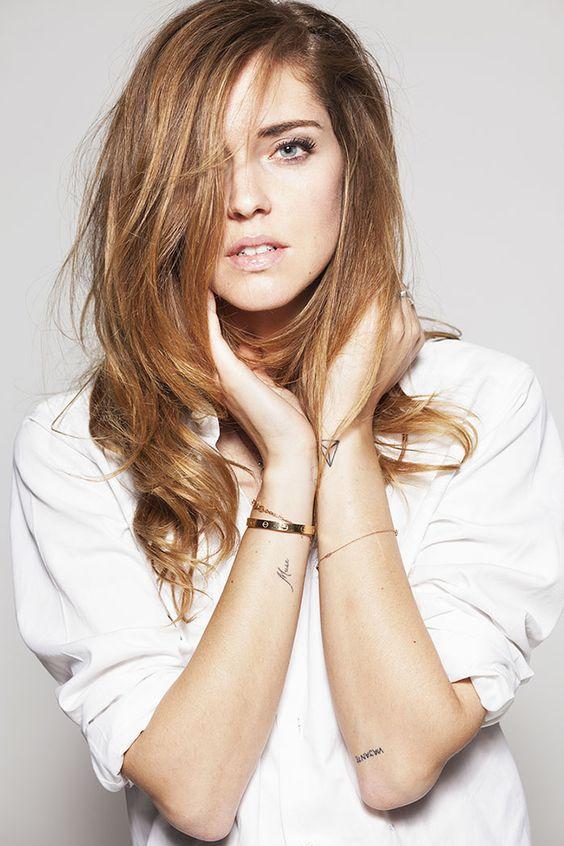 Foto de modelo con tatuaje pequeño de un diamante y un nombre