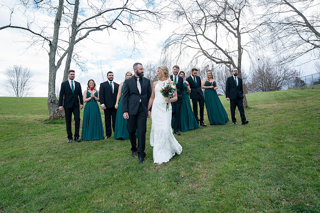 bride and Groom holding hands and looking at each other as they walk forward with bridal party looking from behind Magnolia Farm Asheville Wedding Photography captured by Houghton Photography