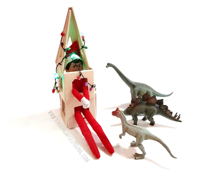 elf on the shelf held captive by dinosaurs