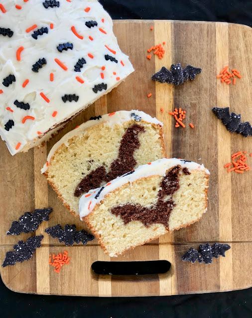 Loaf cake sliced open to reveal a chocolate cake bat inside.