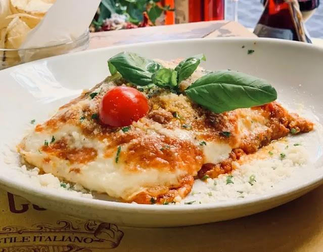 Porción de lasagna servida sobre un plato blanco adornada con hojas de albahaca