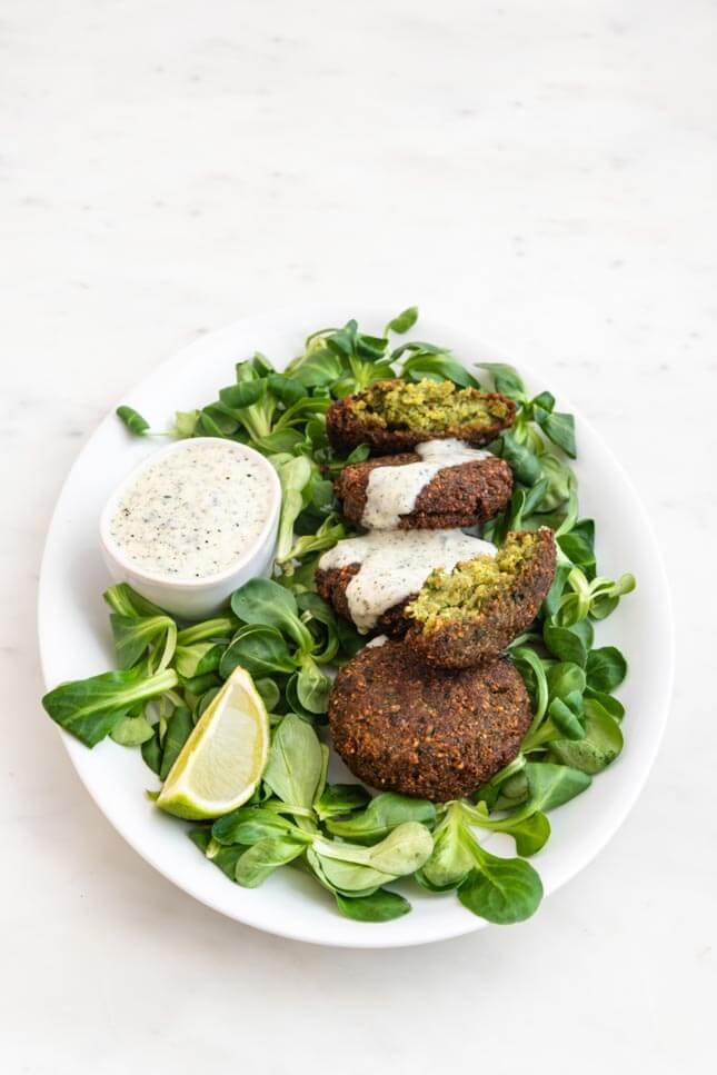 Photo of a plate with falafel decorated with vegetables and vegan yoghurt sauce