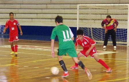 103afe5582a48 O menino com a camisa 11 (verde) tenta criar uma situação de finalização e  a marcação de um gol.