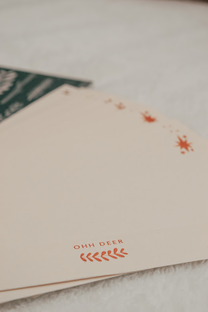 A closeup of cream envelopes with copper foiling of 'Ohh Deer'
