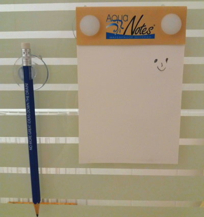 A waterproof notepad with a smiley drawn on it, and a pencil, both hanging on a shower wall