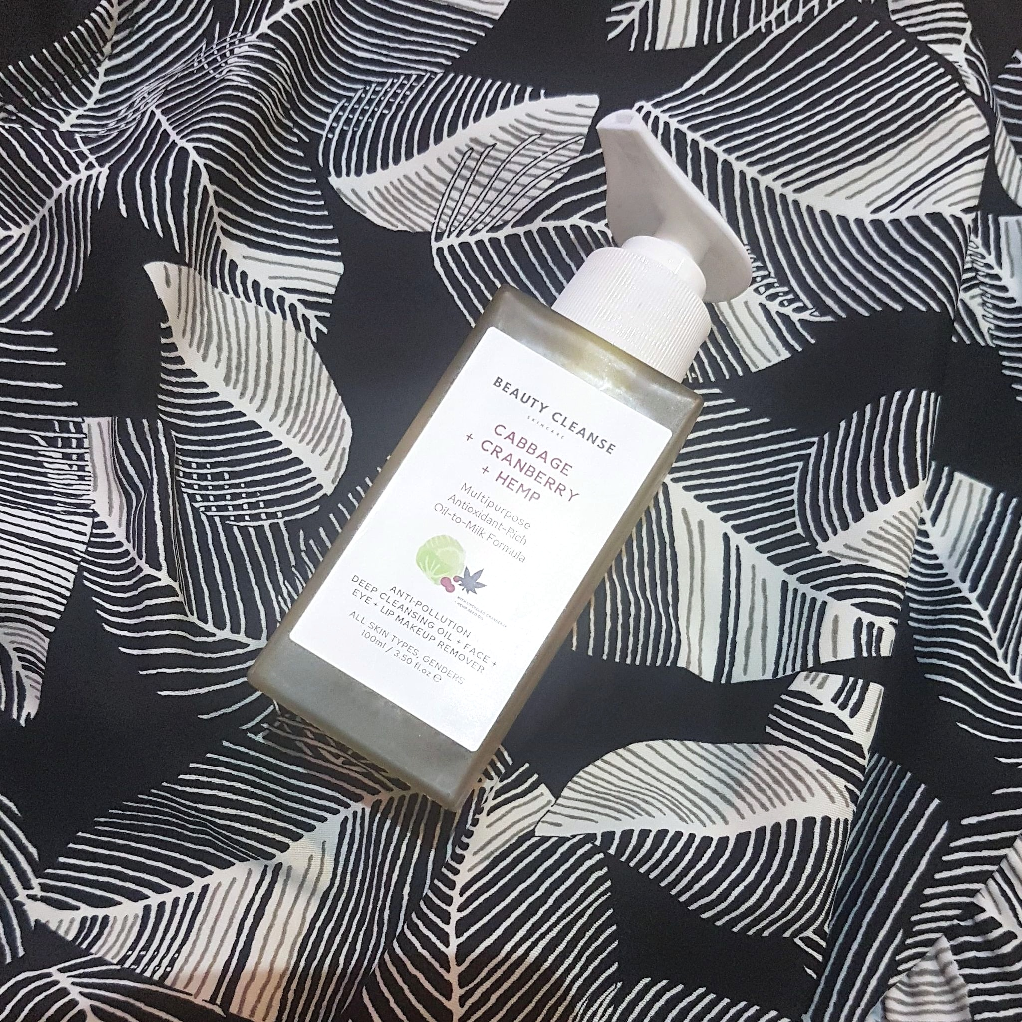 Beauty Cleanse Skincare Cleansing Oil Makeup Remover glass bottle lying down on black and white leaf print background