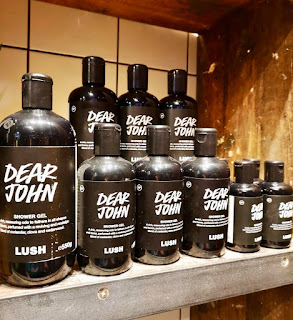 A tall cylindrical plastic bottle filled with dark blue liquid with a black rectangular label with Dear John in bright white font on a rectangular light brown wooden shelf on a bright background