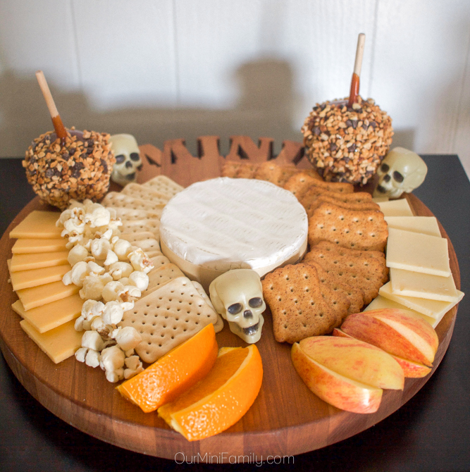 Halloween cheese board with caramel apples, cheese, crackers, fruit, and popcorn