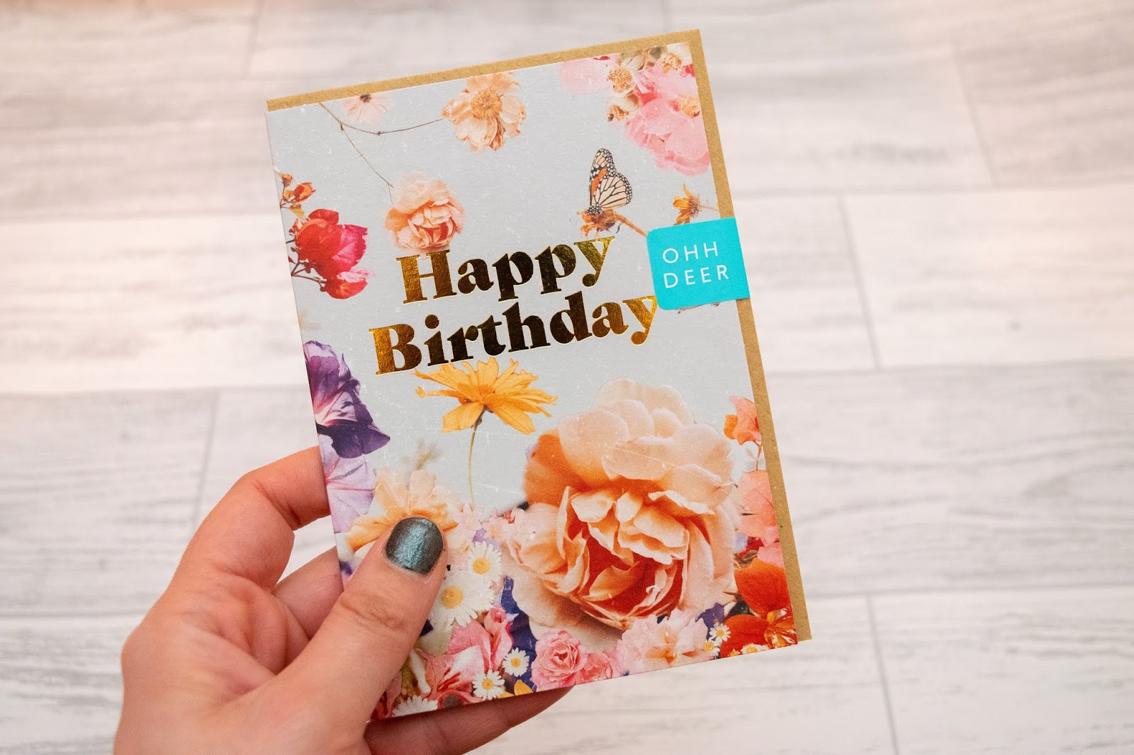 A small birthday card with happy birthday in gold foiling and a flowers on a light blue background.