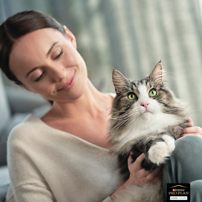 Brunette woman with long-haired grey-and-white cat on lap